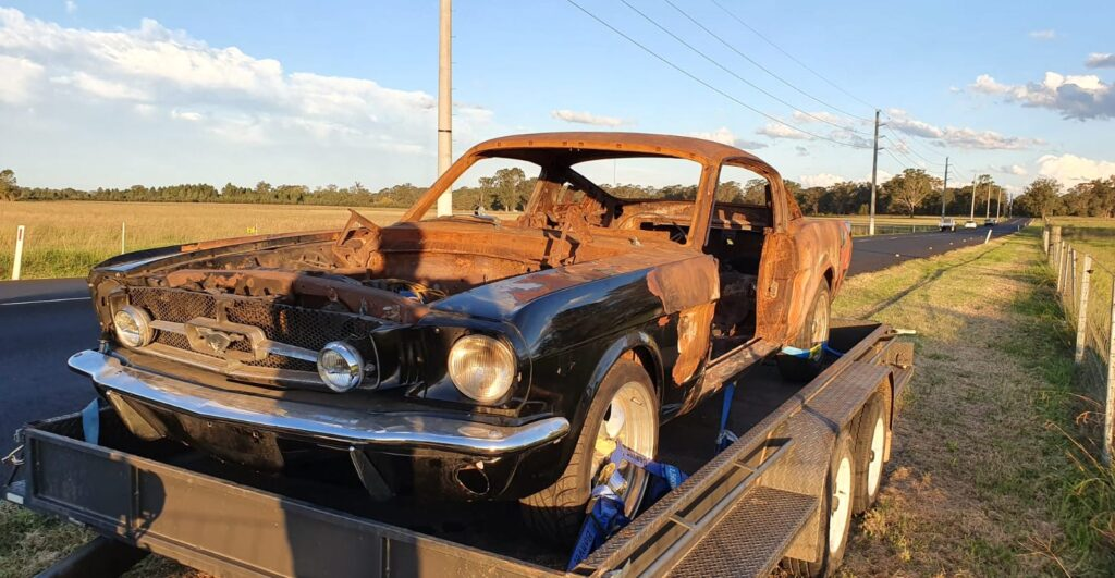 A 1965 Mustang on a flat bed trailer that needs to be restored by Leven Restorations