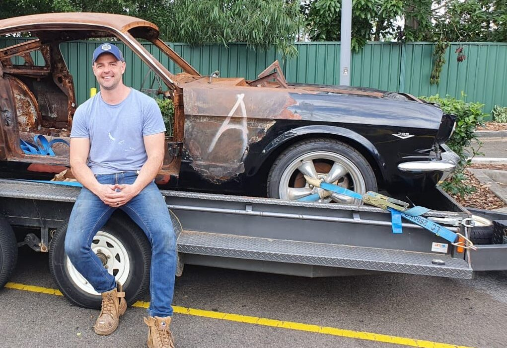 Simon Leven Owner of Leven Restorations sitting on a 1965 Mustang